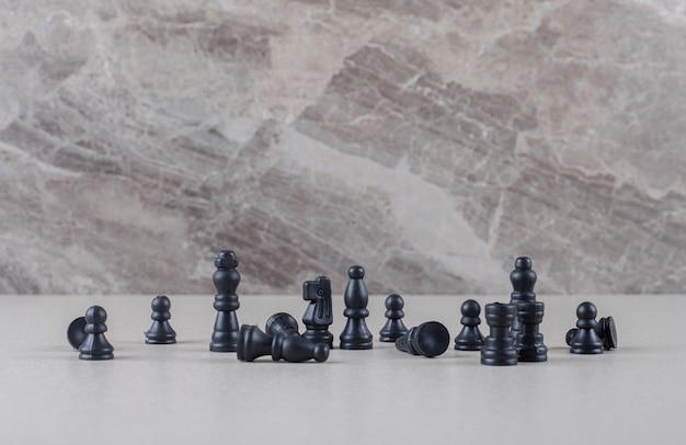 Zwarte schaakstukken weergegeven op marmer