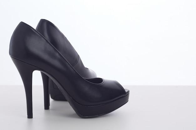 Zwarte schoenen met hoge hakken op wit