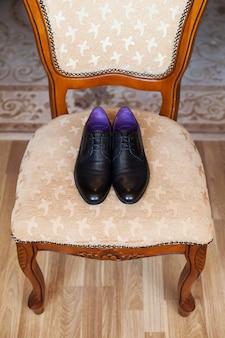 Zwarte schoenen op een stoel. trouwdag.