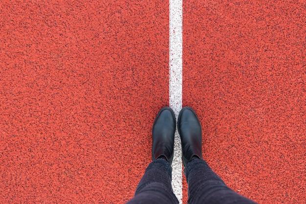Zwarte schoenen staan op de rode asfalt betonnen vloer met witte lijn. voeten schoenen buiten lopen. jeugd selphie moderne hipster