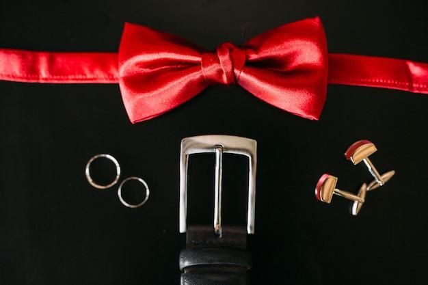 Zwarte schoenen van de bruidegom rode vlinderdas manchetknopen riem