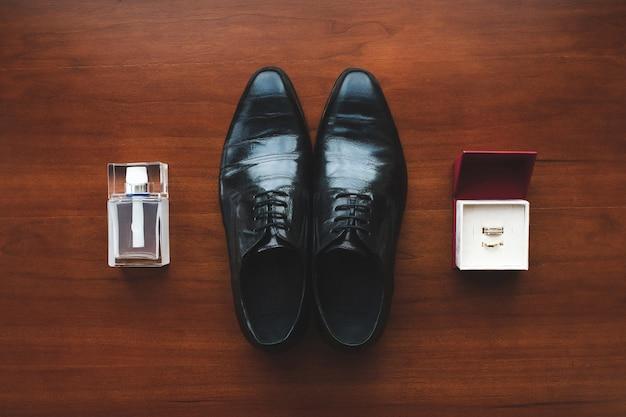 Zwarte schoenen, verlovingsringen en herenparfum op de vloer. accessoires voor de bruidegom op de trouwdag.