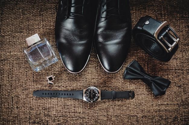 Zwarte schoenen, zwarte riem, zwart horloge, zwarte vlinder, manchetknopen en parfum op een bruine ondergrond met plundering