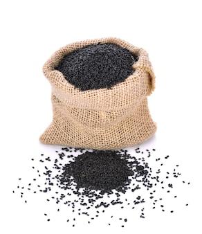 Zwarte sesam in kleine zak is geïsoleerd op een witte achtergrond