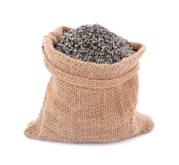 Zwarte sesam schrobt zaad in jute geïsoleerd op een witte ondergrond