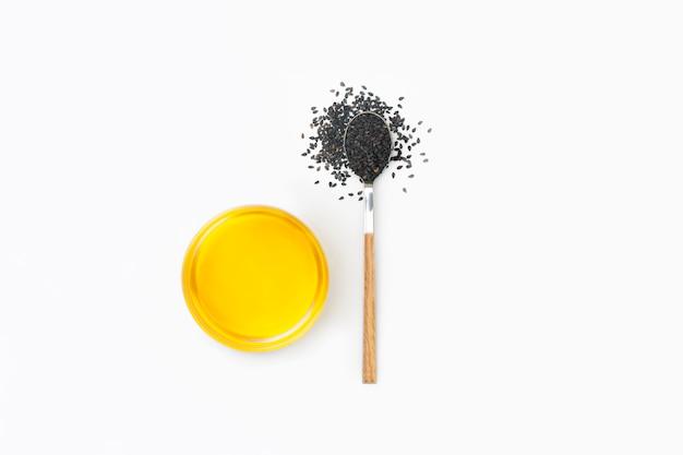 Zwarte sesamolie en sesamzaden op lepel die op witte achtergrond wordt geïsoleerd