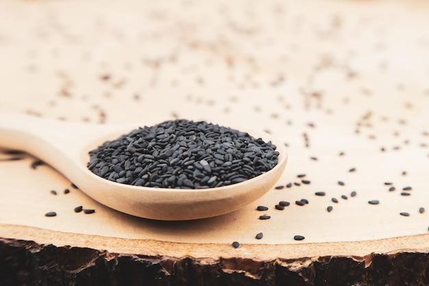 Zwarte sesamzaadjes in een houten lepel voor gezonde voeding en voeding, concepten.