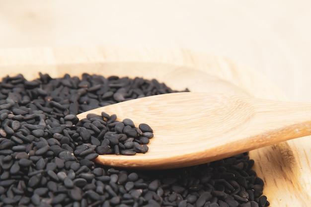 Zwarte sesamzaadjes in een houten lepel.