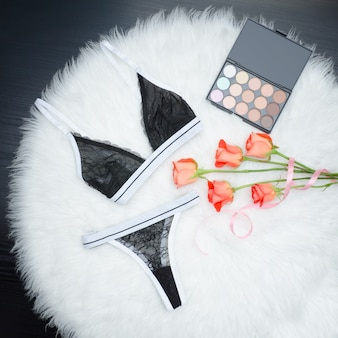 Zwarte set kanten ondergoed op witte vacht. oranje rozen en oogschaduw. modieus concept