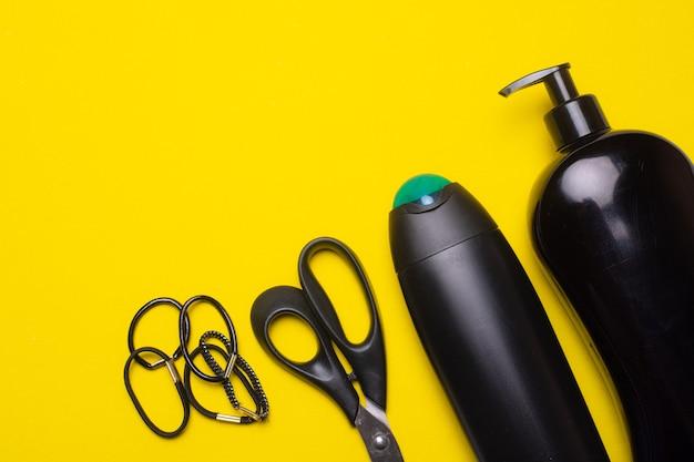 Zwarte shampooflessen, schaar en haarbanden op geel oppervlak