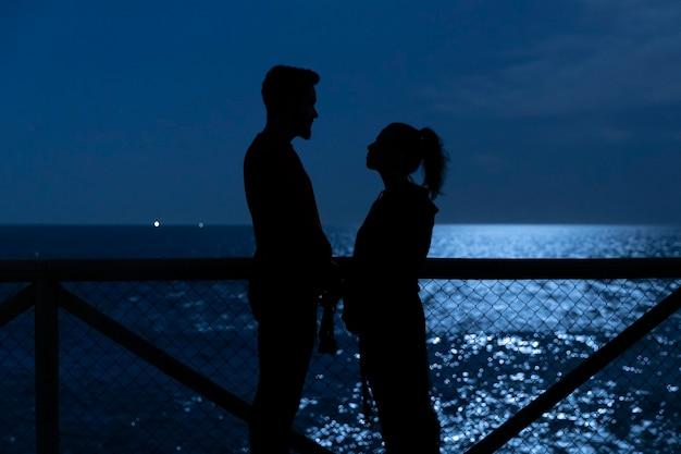 Zwarte silhouetten van een verliefde paar kijken naar elkaar