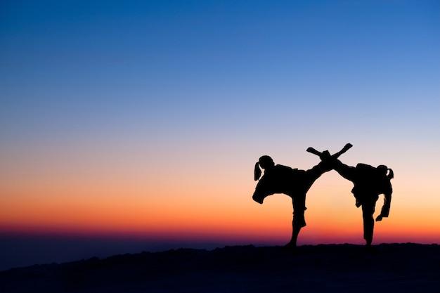 Zwarte silhouetten van jagers op heuvel kruisten hun benen in de strijd tegen avondrood