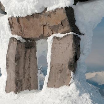 Zwarte slagtand bekeken door een sneeuw bedekt inuksuk, whistler, british columbia, canada