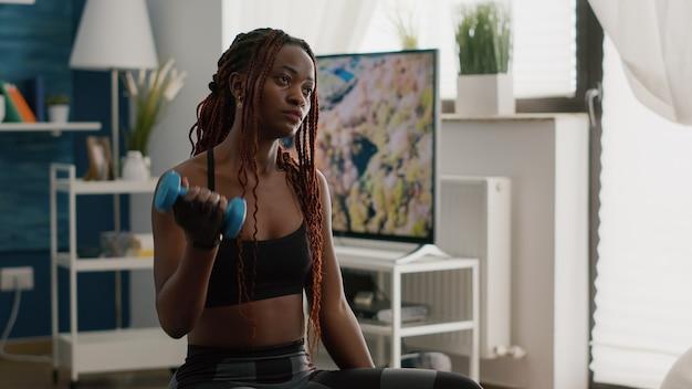 Zwarte slanke vrouw die aerobe oefeningen doet met yogabanden