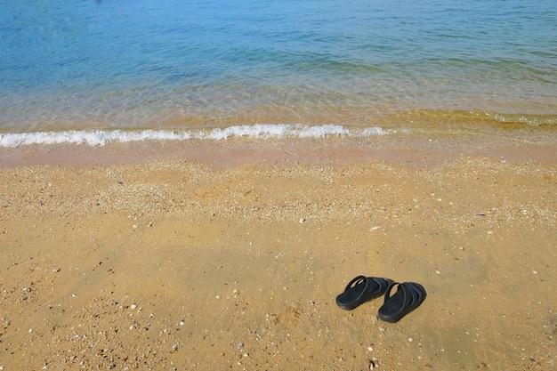 Zwarte slippers op het strand