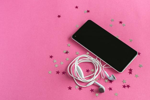 Zwarte smartphone met koptelefoon op een roze achtergrond