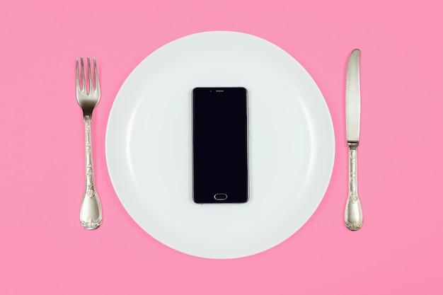 Zwarte smartphone op witte plaat met mes en vork, het concept van de voedsellevering