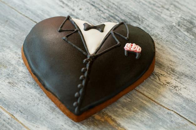 Zwarte smoking hart koekje. bruiloft koekje met glazuur. symbool van belangrijke ceremonie. op een dag zal het leven veranderen.