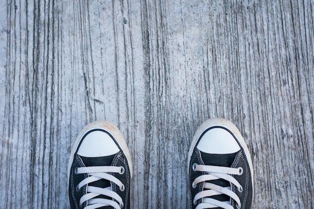 Zwarte sneakers met hipster man op beton