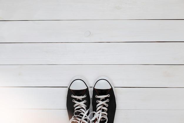 Zwarte sneakers met veters op een bovenaanzicht van een witte houten vloer