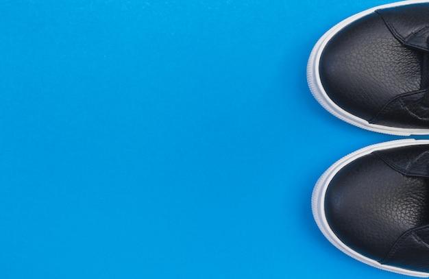 Zwarte sneakers op blauwe achtergrond. plat lag, bovenaanzicht minimale achtergrond.