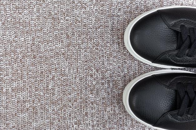 Zwarte sneakers op wollen achtergrond. plat lag, bovenaanzicht. mode blog concept. ruimte voor tekst kopiëren
