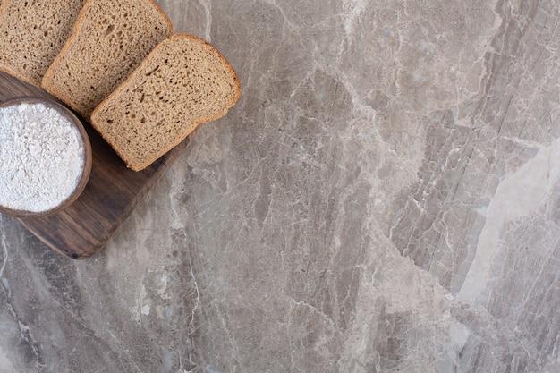 Zwarte sneetjes brood en een kom met bloem op een bord op marmer.