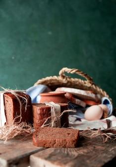 Zwarte sneetjes brood gewikkeld met wit papier en rustieke draad met een pot melk, eieren en knoflook op een witte handdoek in een mandje.