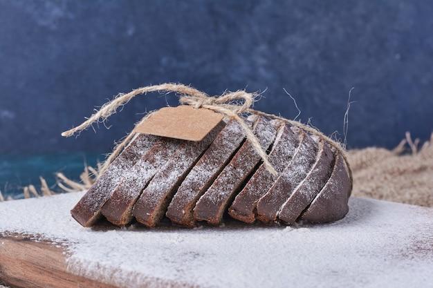 Zwarte sneetjes brood met tag op hen op blauwe tafel.
