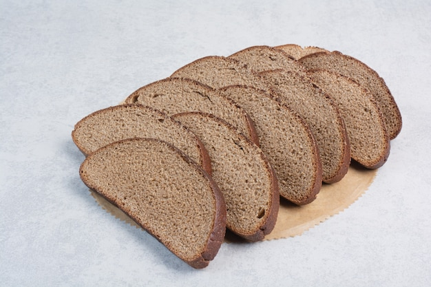 Zwarte sneetjes brood op vel papier