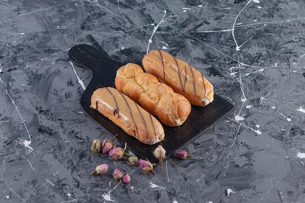 Zwarte snijplank van heerlijke eclairs op marmeren tafel.
