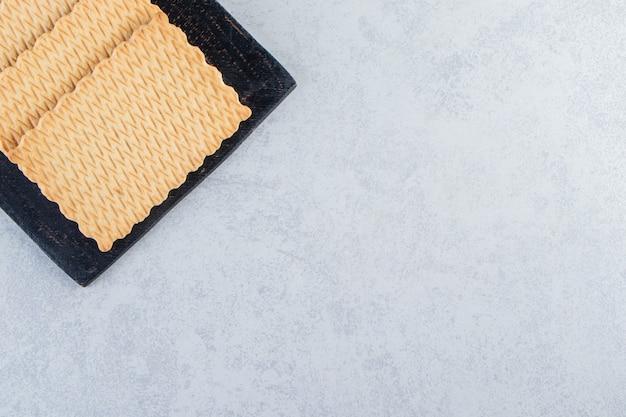Zwarte snijplank van smakelijke koekjes geplaatst op stenen achtergrond.