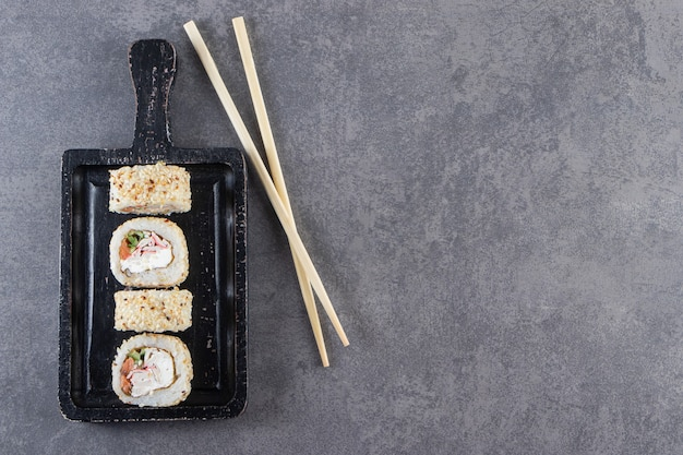 Zwarte snijplank van sushi rolt met sesamzaadjes op stenen achtergrond.