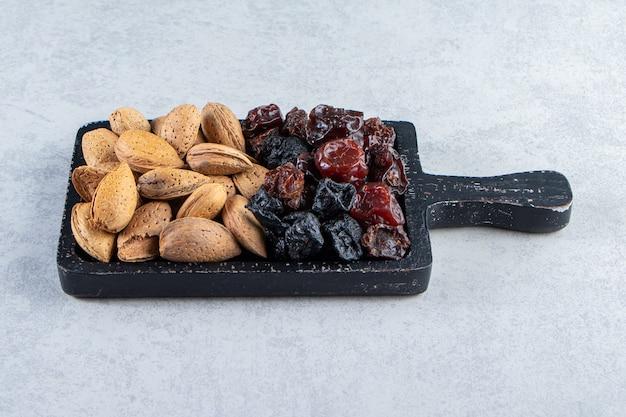 Zwarte snijplank vol droge dadels en noten op stenen achtergrond.