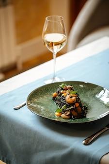Zwarte spaghetti met zeevruchten en saffraansaus met witte wijn