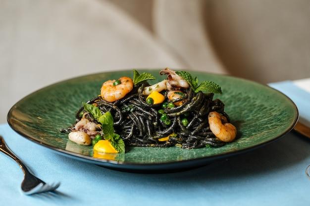 Zwarte spaghetti met zeevruchten en saffraansaus op de blauwe tafel