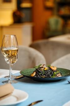 Zwarte spaghetti met zeevruchten en saffraansaus op de houten tafel