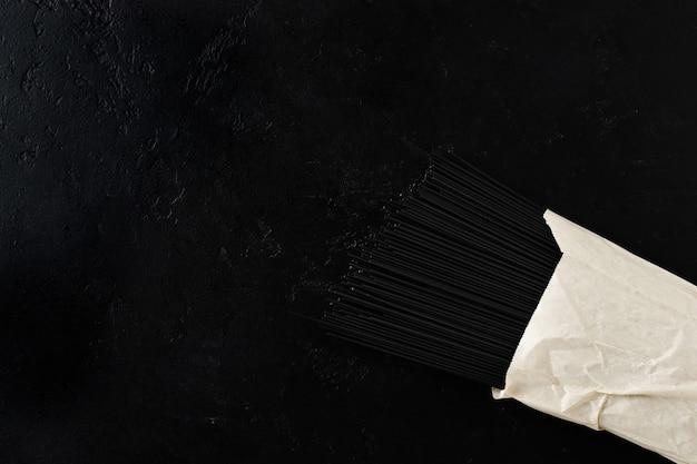 Zwarte spaghettideegwaren met inktvisinkt in een papieren zak op een zwarte betonnen ondergrond