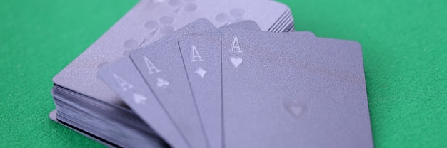 Zwarte speelkaarten met azen liggen op groene speeltafel gokkaartspellen voor geldconcept