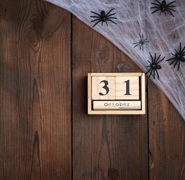 Zwarte spinnenbeeldjes en houten retro klok gemaakt van blokken met de datum van 31 oktober