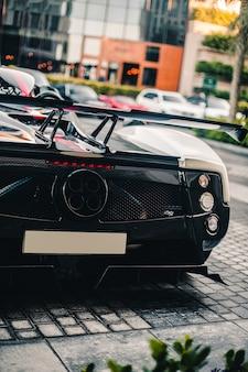Zwarte sportwagen achter vire, motor gasleidingen, lege ruimte voor registratienummer.