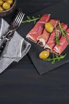 Zwarte stenen schotel met plakjes gerookte ham of spaanse jamon serrano of italiaanse prosciutto crudo