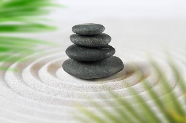 Zwarte stenen stapelen zich op in het zand achter palmbladeren. zen japanse tuin
