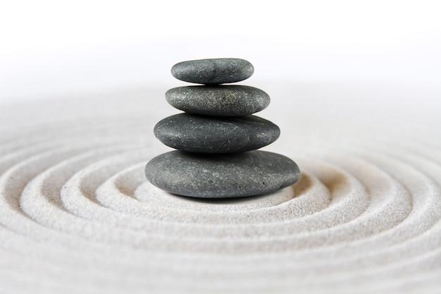 Zwarte stenen stapelen zich op in het zand