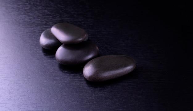 Zwarte stenen voor thai spa op zwarte houten achtergrond