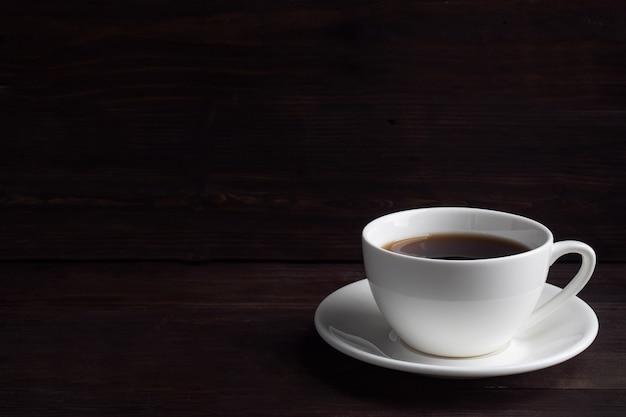 Zwarte sterke espressokoffie in een witte ceramische kop. houten donker.