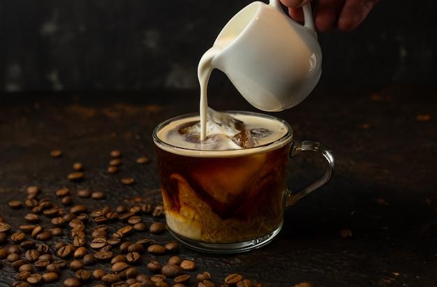 Zwarte sterke ijskoffie met zware room op een donker oppervlak