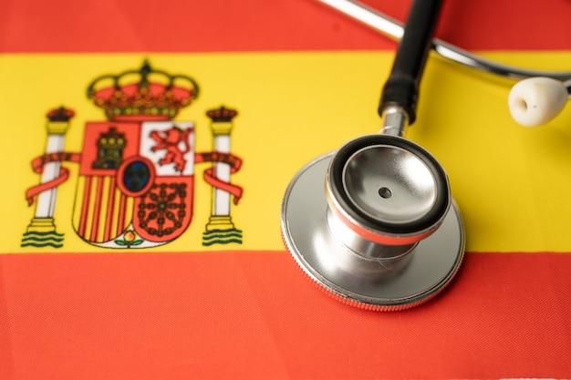 Zwarte stethoscoop op de vlagachtergrond van spanje, zaken en financiënconcept.