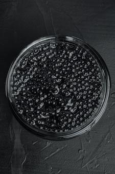 Zwarte steur kaviaar pot, op zwarte tafel, bovenaanzicht plat lag