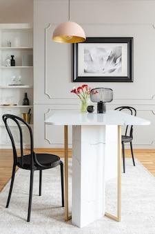 Zwarte stoel aan tafel met bloemen in witte eetkamer interieur met poster en lamp. echte foto
